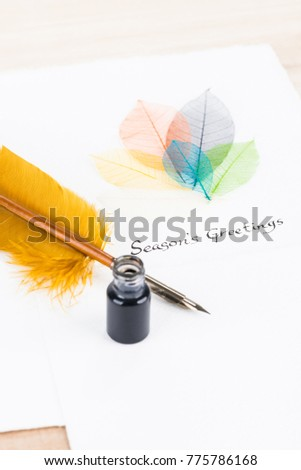 Season's Greetings message with quill pen and leaves on cotton paper close up