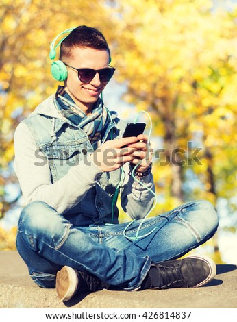 season, technology, lifestyle and people concept - smiling young man or teenage boy in headphones with smartphone listening to music over autumn park background