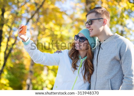 season, vacation, holidays, technology and friendship concept - smiling couple with smartphone taking selfie over autumn park background - stock photo