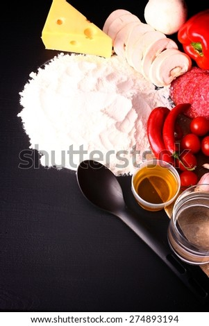 Seasonal black table with products for pizza - stock photo