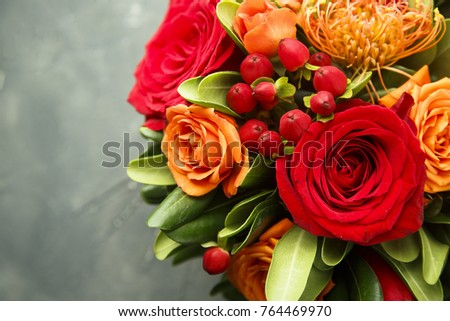 Seasonal bouquet with red and orange flowers and wild berries