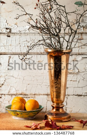 Seasonal centerpiece of a mercury glass copper vase with branches and autumn leaves in a rustic shabby chic setting - stock photo