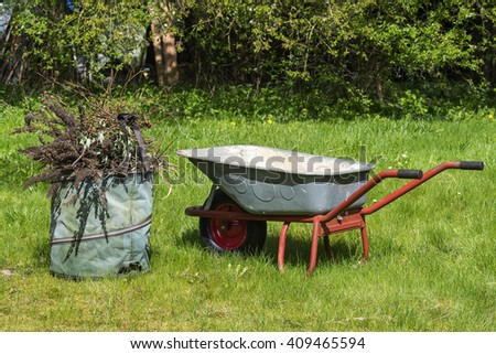 seasonal cleaning in the garden, wheelbarrow and compost sack on the lawn - stock photo