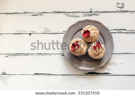 seasonal cupcake with autumn leaves on white vintage wooden background - stock photo