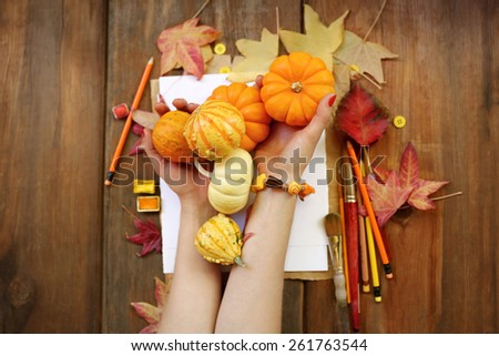 Seasonal fall time composition with hands wearing a bracelet and holding orange pumpkins over autumn leaves placed next to a white sheet of paper, pencils and watercolor on top of brown vintage wood - stock photo