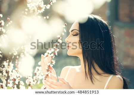 Seasonal feature, beauty and fashion. Beautiful woman near apricot blooming tree.