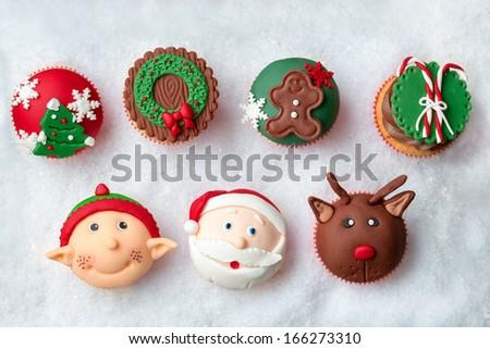 Seasonal festive Christmas mini dessert cupcakes in traditional decorative symbols elements - stock photo