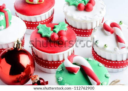Seasonal festive christmas mini dessert cupcakes in traditional red green decorative symbols elements - stock photo
