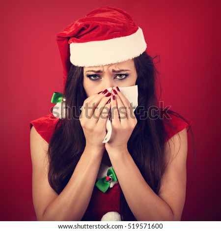 Seasonal flu. Unhappy frustration sick woman holding paper tissue near her nose and looking down in christmas night on red background. Closeup portrait
