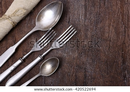 Seasonal old wooden table with cutlery - stock photo