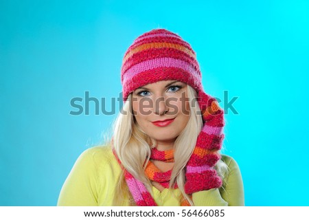 Seasonal portrait of pretty funny woman in hat and gloves smiling. blue background