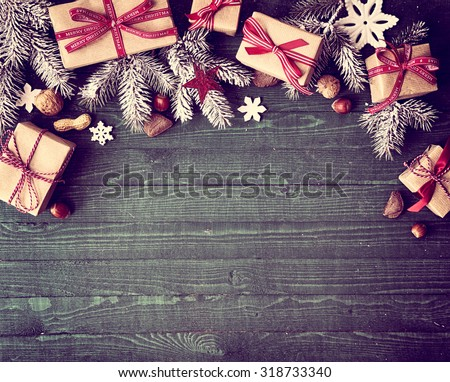 Seasonal rustic Christmas border composed of decorative gifts, pine branches, nuts and snowflake ornaments over a wooden background with copyspace, overhead view - stock photo