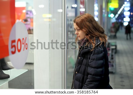 Seasonal sale, young woman looking through shop window to shoes