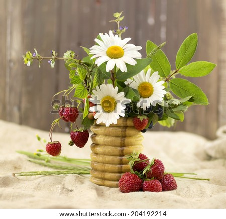 Seasonal still life with summer flowers and strawberries - stock photo