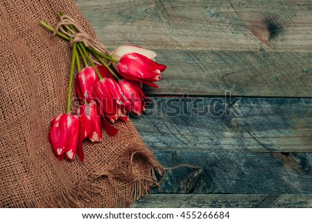 seasonal tulip flower bouquet red color on green stem in spring with rope and burlap on blue wooden background, closeup, copy space