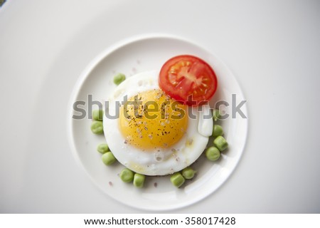 Seasoned egg with tomato and peas served on a plate. This recipe is delicious to taste and can be done in a couple of minutes. The nutrients value are awesome and super-rich. - stock photo