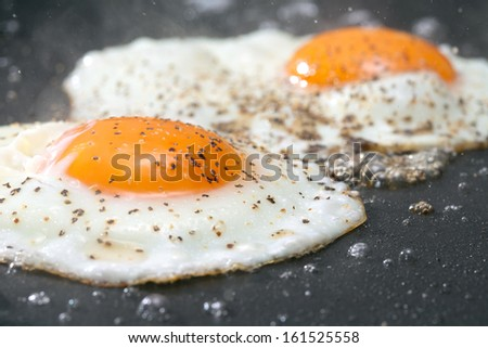 Seasoned eggs frying on a pan. - stock photo