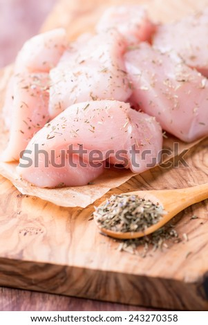 Seasoned raw chicken breast fillets over wooden board, selective focus - stock photo