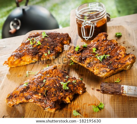 Seasoned ribs on a rustic wooden picnic table at a BBQ in the garden with fresh herbs and a glass jar of spicy marinade or basting sauce - stock photo