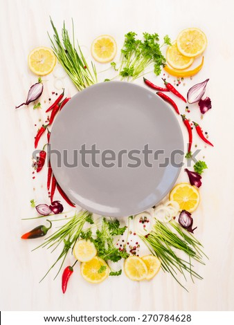 seasoning and spices around empty gray plate on white wooden background, top view, copy space - stock photo