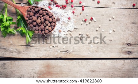 Seasoning for cooking. Allspice pepper in wooden spoon and sea salt, red pepper and herb parsley  on aged wooden background. Food ingredient. Selective focus. Place for text. Flat lay. Toned image. - stock photo
