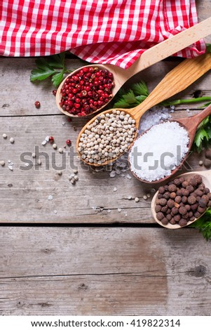 Seasoning for cooking. Red, white and allspice pepper and sea salt in wooden spoon on aged wooden background. Food ingredient. Selective focus. Place for text. Flat lay. Top view. Vertical image. - stock photo