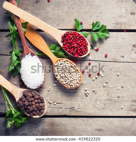 Seasoning for cooking. Red, white and allspice pepper and sea salt in wooden spoon on aged wooden background. Food ingredient. Selective focus.  Flat lay. Top view. Square image. - stock photo