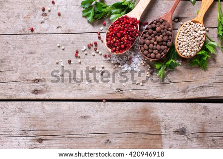 Seasoning for cooking. Red, white and allspice pepper  in wooden spoons on aged wooden background. Food ingredient. Selective focus. Flat lay. Top view. Place for text. - stock photo