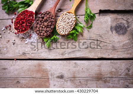Seasoning for cooking. Red, white and allspice pepper  in wooden spoons on aged wooden background. Selective focus. Flat lay. Top view. Place for text. - stock photo