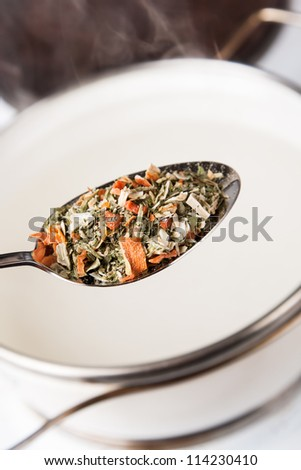 seasoning in spoon for cooking soup in pot with steam - stock photo