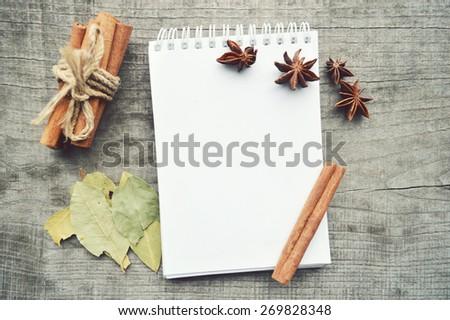 seasonings,spices,recipe book,Notepad,write,pepper, peas,red pepper,black pepper,cardamom,star anise,cinnamon,coriander,cinnamon sticks,cloves,star  - stock photo
