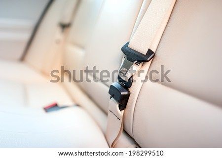 Seat belt on rear seat of modern car with beige leather interior - stock photo