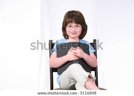seated brunette girl with glasses holding book