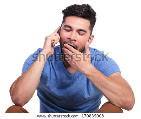 seated casual man is being bored by the phone conversation - stock photo