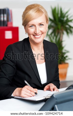 Seated female secretary writing on notepad in office and looking at you - stock photo