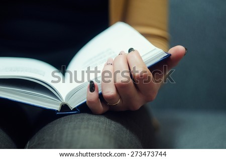 Seated girl reading a book  - stock photo