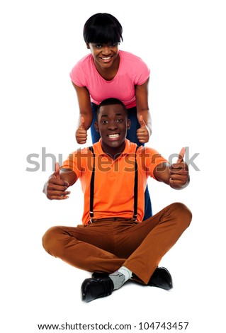 Seated man and standing woman showing double thumbs-up gesture isolated against white