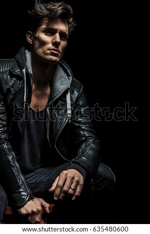 seated man in leather jacket dreaming away on dark background