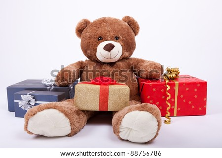 Seated teddy bear with gift boxes, over a white background