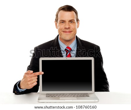 Seated young businessman pointing at blank laptop screen. Laptop facing camera - stock photo