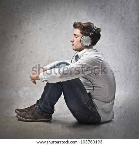 Seated young man listening to music