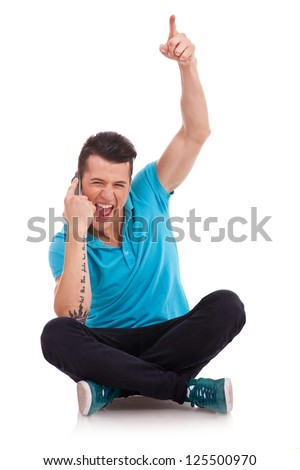 seated young man talking on the phone and cheering, on a white background - stock photo