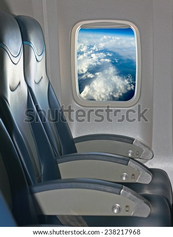 Seating and window inside an aircraft with view of blue sky and clouds