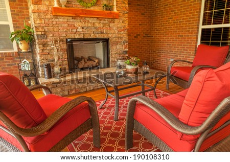 Seating area around gas stone fireplace on a covered backyard deck - stock photo
