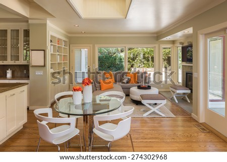 Seating arrangement in modern kitchen with cherry wooden floor and open ceiling. Kitchen in white with granite counter tops with stainless steel oven and stove. - stock photo