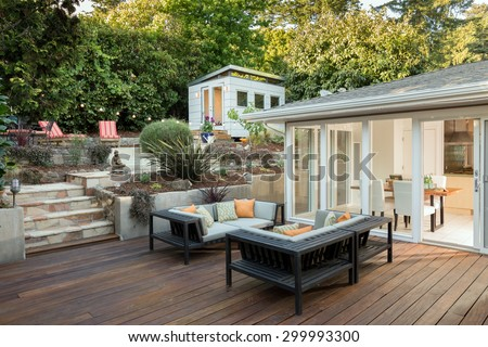 Seating arrangement, woven couch and sofa in front of contemporary home with open folding doors, wooden terrace in Zen Garden style with open floor plan and guest house. - stock photo