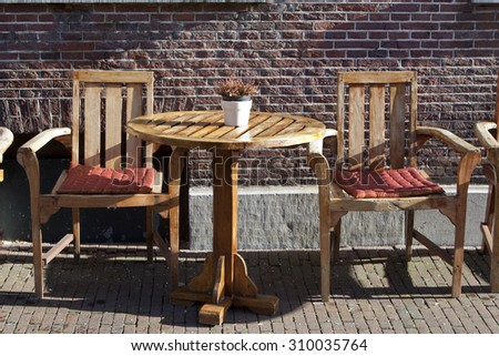 Seats waiting for a city break at a sidewalk cafe in Delft, the Netherlands  - stock photo