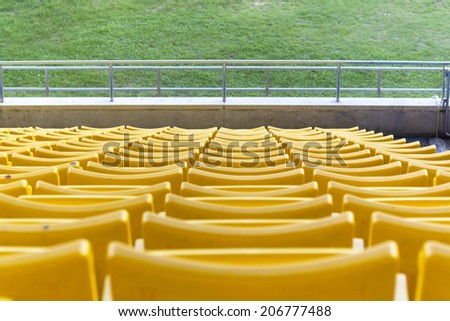 Seats yellow on the sidelines before the start of the competition. - stock photo