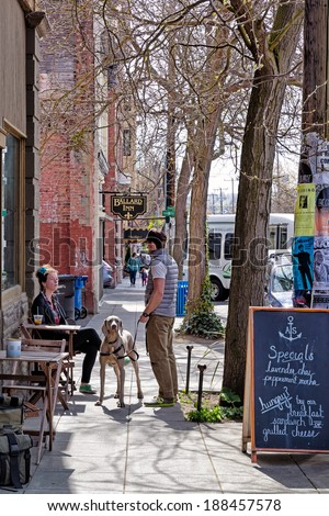 SEATTLE-APR 15, 2014: Coffee drinkers at a sidewalk cafe in Ballard, a popular neighborhood in Seattle known for its historic architecture and a growing scene of hip restaurants, bars and shops. - stock photo