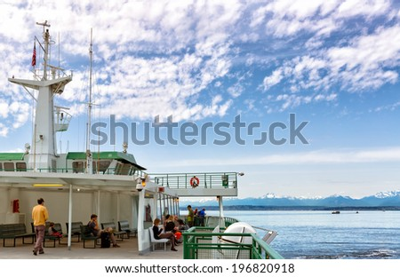SEATTLE-APR 14,2014:Seattle ferry to Bainbridge Island, with a view of the snow capped Cascades.Washington has the nation's largest ferry system with 23 million riders and 10 million vehicles a year. - stock photo